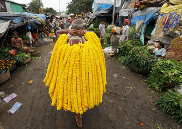 A vendor sells garlands of marigold flowers on Janamashtmi