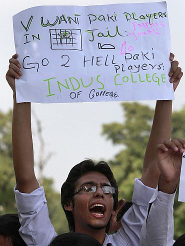 A Pakistani student holds a placard as he shouts slogans against national cricket team players who are involved in a match fixing scandal, during a protest in Islamabad