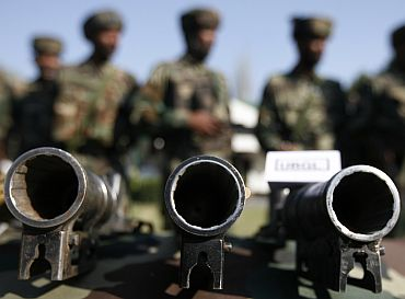 Army soldiers stand behind seized a display of under barrel grenade launchers (UBGL) during a news conference in a garrison in Srinagar