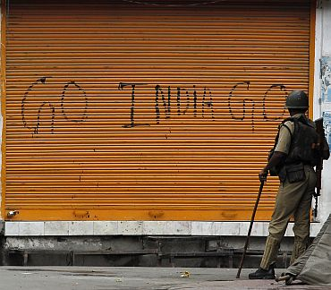 A policeman stands guard in front a closed shop marked with graffiti during a curfew