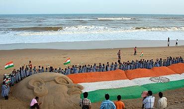 School children gather around a sand sculpture of the Indian national flag and Mahatma Gandhi