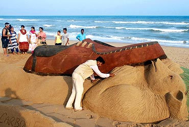 A sand sculpture of 'a polar bear being crushed by a shoe' to mark World Environment Day