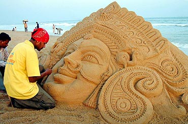 Patnaik, a sand artist, creates a sculpture of Goddess Durga in Puri