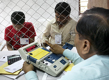 An election official prepares to count ballots inside a counting centre in Gandhinagar, Gujarat