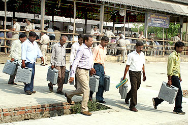 Election officials carry electronic voting machines for counting in Allahabad