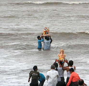 People immersing Ganesh idols in the sea