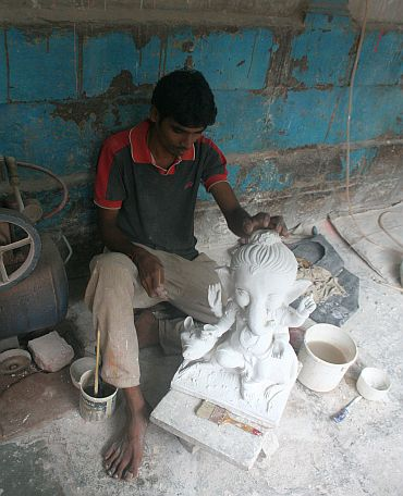 A worker creates a Ganesh idol using PoP