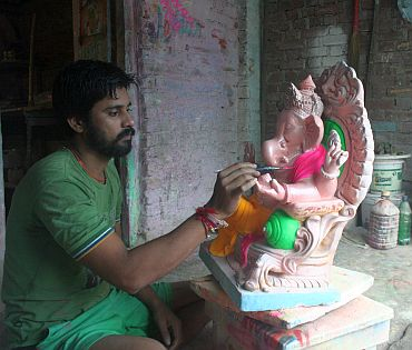Dinesh Dhamne works on a Ganesh idol
