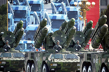 People's Liberation Army rocket launcher trucks rumble past Tiananmen Square