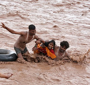 Rescuers help a woman to move a safer place from flooded Ghaghar river after heavy rains in Punchkula in Haryana