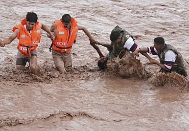 Rescuers help a woman to move a safer place from flooded Ghaghar river after heavy rains in Punchkula, Haryana