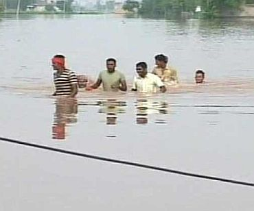 People wade through neck-deep flood waters