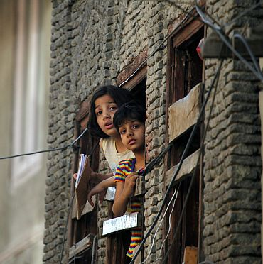 Children look out of a window of their home during a curfew in Srinagar