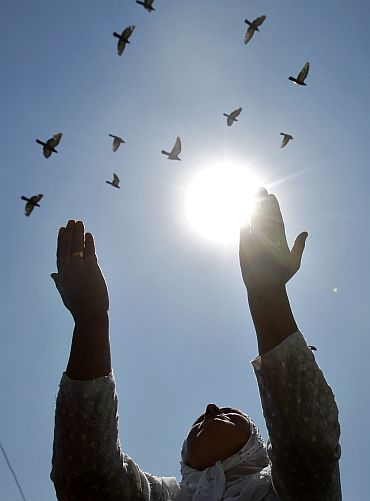 Pigeons fly past as a Kashmiri woman prays