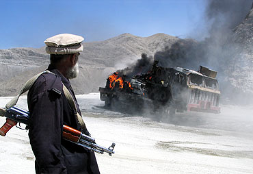 A Pakistani security official stands near a burning vehicle after it was attacked in Balochistan