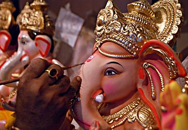 An artist gives finishing touches to a Ganesha idol