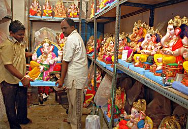 Shopkeepers stocking up ready Ganesha idols in a workshop