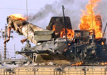 A British soldier jumps from a burning tank which was set ablaze after a shooting incident in the southern Iraqi city of Basra on September 19, 2005