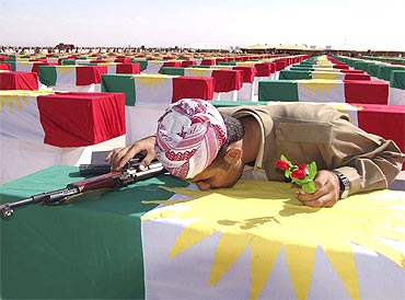 A Kurdish Peshmerga soldier kisses the coffin of a person killed during former Iraqi President Saddam Hussein's rule at a ceremony in Arbil's airport, northern Iraq, on October 17, 2005