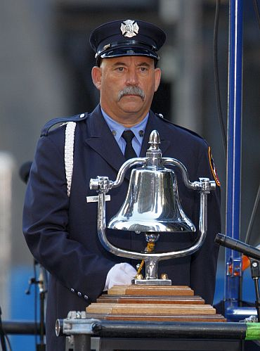 Fire Fighter James Sorokac rings the bell at 8:46am, starting a moment of silence observing the time the first plane struck the North Tower of the World Trade Centre, at the ninth anniversary remembrance of the attacks on New York and Washington, in New York