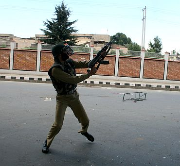 A policeman fires warning shots to disperse the mob