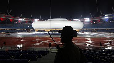 A guard keeps watch over the giant aerostat inside the Jawaharlal Nehru stadium in New Delhi