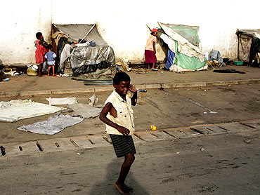 A homeless boy plays in front of makeshift huts in Nosybe outside Antananarivo, Madagascar