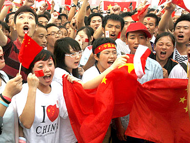 People shout slogans praising China during a flag-raising ceremony at Tiananmen Square in Beijing