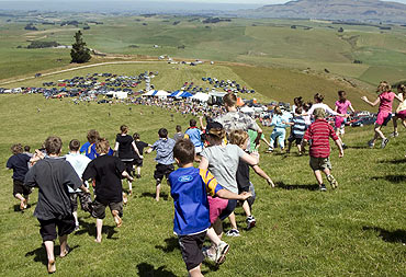 Competitors participate in a race at the Whitestone Cheese Rolling contest in New Zealand