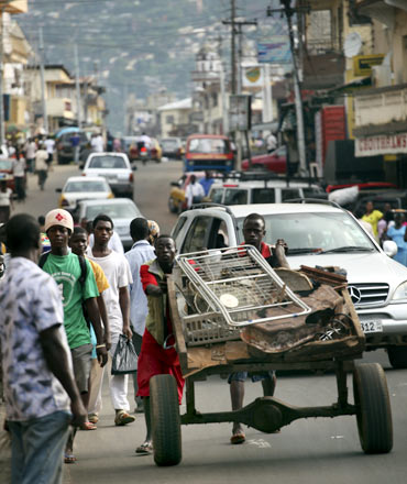 A Sierra Leonian man pushes a handcart in downtown Freetown