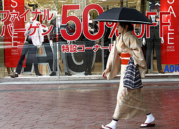 A woman walks past a shop holding a bargain sale at a shopping district in Tokyo