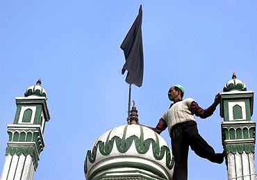 A man hoists a black flag atop a mosque in Ayodhya to observe the anniversary of Babri demolition