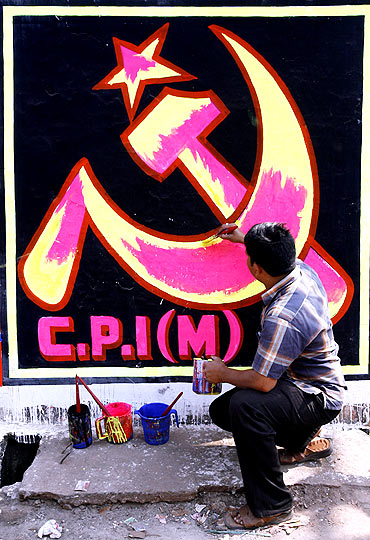A CPM worker paints his party's symbol on a wall in Siliguri