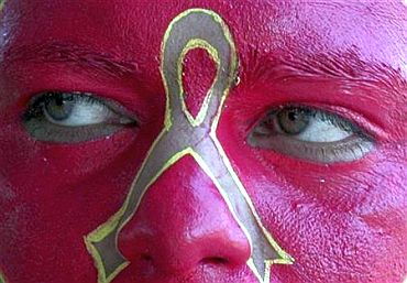 A social activist displays an AIDS symbol on his face during an awareness campaign in Chandigarh