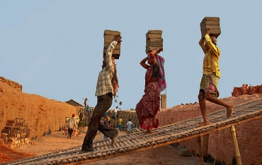A woman joins her two male co-workers at a brick kiln