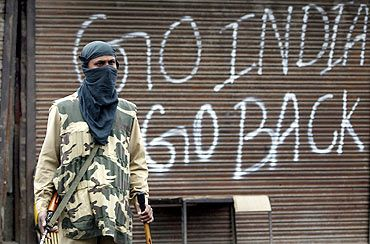 A policeman stands guard near a closed shop during a curfew in Srinagar