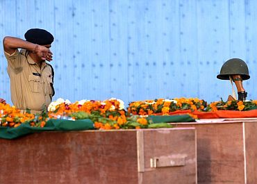 A CRPF jawan pays his last respects near the coffins of his colleagues who died in a Maoist attack in Chattisgarh