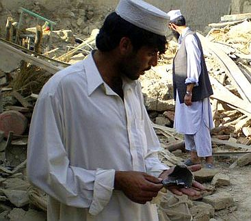 Villagers pick up rocket fragments after a drone strike