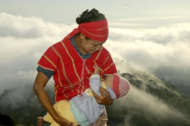 Ma Sun breastfeeds her nine-month-old son standing atop Golden Rock