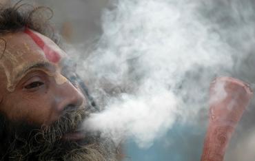 A sadhu smokes marijuana in Allahabad