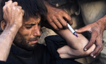 An addict has heroin injected by a friend in Herat in western Afghanistan