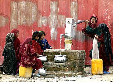 Afghan women collect drinking water from a handpump in a village near Kabul.