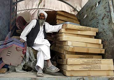 A worker waits to unload election materials from a truck at a polling centre outside Kabul.