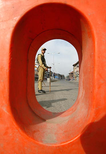 A policeman stands guard on a deserted road during a curfew in Srinagar