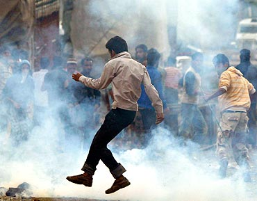 A Kashmiri protester runs for cove