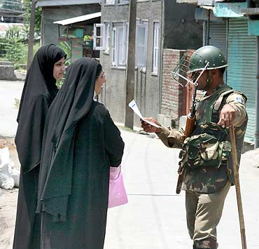 A policeman gives directions to women in Srinagar