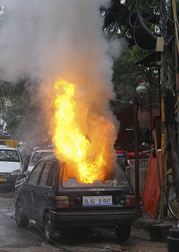 A car that burst into flames is pictured near the scene of the shooting