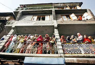 Women watch the funeral procession of a Kashmiri youth who was killed during an anti-India protest