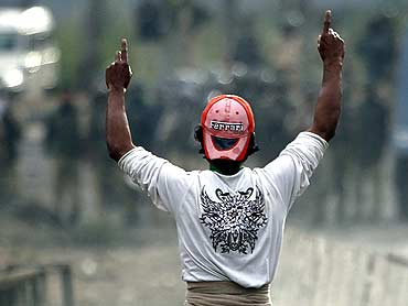 A Kashmiri protester gestures towards policemen during an anti-India protest in Srinagar