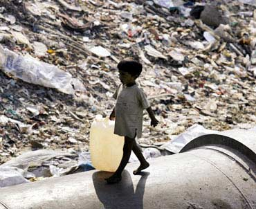 A boy walks past a garbage dump in Mumbai